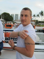 Jason Barrett flexing, showing arm tattoo