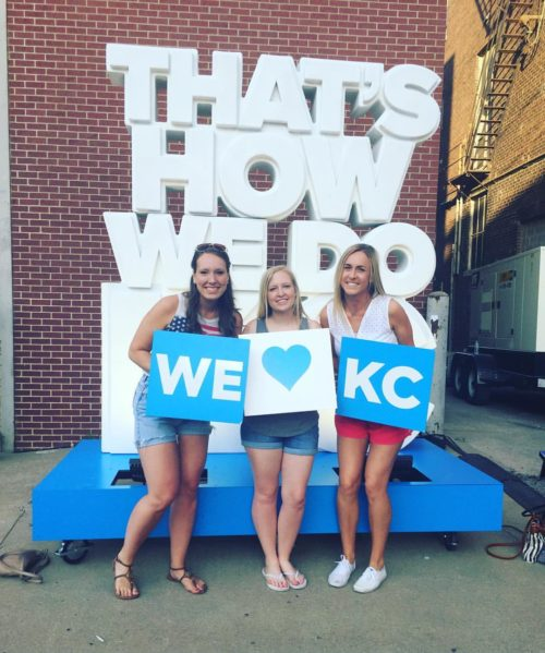 """Taylor Russo and two friends in front of """"That's how we do KC"""" sign"""