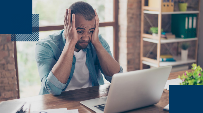 Frustrated young man with sad grimace in front of his laptop with his hands on his head