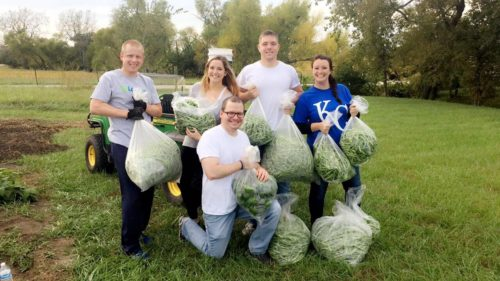Five people holding bags of recently picked green beans